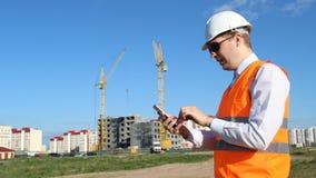 Hauptinspektor in Kaugummi der schwarzen Gläser und Klettern im Telefon auf dem Hintergrund des Bauens eines Hauses stock video footage