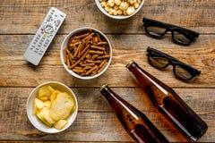 Hauptpartei mit Fernsehaufpassen, -Snäcken und -bier auf Draufsicht des hölzernen Hintergrundes lizenzfreies stockfoto
