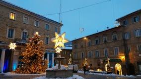 Hauptplatz von Urbino verzierte mit Weihnachtsbaum und Sternen mit Schnee an der Dämmerung stockfotografie