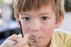 Hauptporträt des reizenden und süßen Jungen 7 oder 8 Jahre alt im gelben Hemd, das glücklichen trinkenden Eiscreme Smoothie genie Stockfotos
