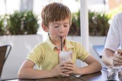 Hauptporträt des reizenden und süßen Jungen 7 oder 8 Jahre alt im gelben Hemd, das glücklichen trinkenden Eiscreme Smoothie genie Stockfotografie