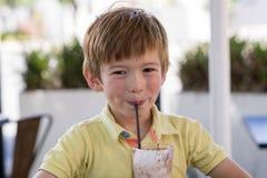 Hauptporträt des reizenden und süßen Jungen 7 oder 8 Jahre alt im gelben Hemd, das glücklichen trinkenden Eiscreme Smoothie genie Stockfoto
