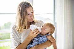 Hauptporträt eines Babys mit der Mutter, die ihr Kind von der Flasche einzieht lizenzfreie stockfotos