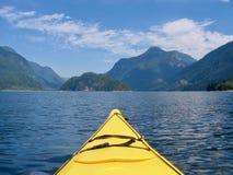 Hauptpunkte eines gelben Kajaks zu den schönen Bergen und zum Ozean lizenzfreie stockbilder