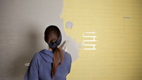 Hauptreparatur Das M?dchen verbreitet den Gips auf der Wand mit einer gro?en Metallspachtel, um den Gipsf?ller auf der Wand auszu stock video
