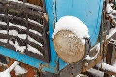 Hauptscheinwerfer der alten Traktornahaufnahme bedeckt mit Schnee im Winter Lizenzfreie Stockbilder