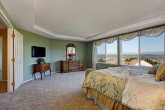 Hauptschlafzimmer mit grünen Wänden, Eitelkeitskabinett und Blumenbettwäsche Lizenzfreies Stockbild