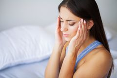Hauptschmerz Attraktive junge Frau auf ihrem Bett aufwachen, das unglücklich schaut und krank sich fühlt stockfotos