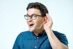 Hauptschuß des Mannversuchens hören Klatsch oder Nachrichten Getrennt auf Grau stockbild