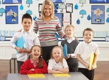Hauptschulkinder und Lehrer am Schreibtisch Stockfotografie