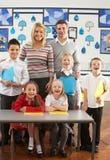Hauptschulkinder und Lehrer am Schreibtisch Lizenzfreie Stockbilder