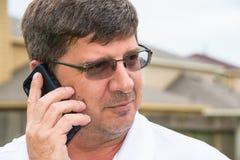 Hauptschuss-Mann, der am intelligenten Handy hört Lizenzfreie Stockfotos
