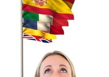 Hauptsprachflaggen über Vordergrund der Frau des blonden Haares, die oben schaut Stockfotografie