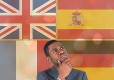 Hauptsprachflaggen überschneiden mit Goldlichtern um das Denken des jungen Mannes Stockfotografie