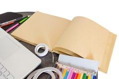 Haupttabelle mit Satz bunten Versorgungen, leeres braunes Notizbuch Lizenzfreies Stockbild