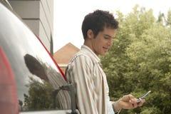 HauptTechnologie-Mann mit Handy mit Auto Stockfotos
