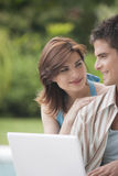 HauptTechnologie-Paare mit Laptop im Garten Stockfotos