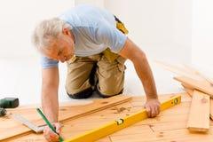 Hauptverbesserung - Mann, der hölzernen Fußboden installiert Stockbild