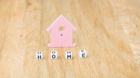 HAUPTwort von Würfelbuchstaben vor Flieder färbte Haussymbol auf Holzoberfläche Stockfotografie
