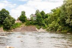 Haus auf dem Fluss nahe Berg Lizenzfreie Stockfotografie