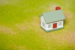Haus auf einem Gras Haus gebildet vom Geld im schwarzen Hintergrund Stockfotos