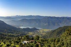 Haus auf einem Hügel, vor dem hintergrund der Stadt von Pokhara in einem Gebirgsnebeligen Morgental mit Phewa See unter einem fre stockbilder