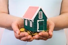 Haus auf einem Stapel des Geldes in den Frauenhänden Lizenzfreies Stockbild
