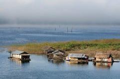 Haus auf Floss im See Stockfotografie