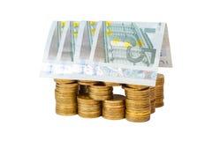 Haus aufgebaut von den Münzen und von Banknoten getrennt Stockbild