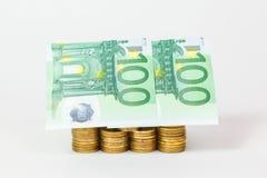 Haus aufgebaut von den Münzen und von den Banknoten   Lizenzfreie Stockfotos