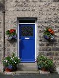 Haus: blaue Haustür mit Blumen lizenzfreies stockfoto