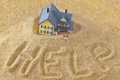 Haus, das in Treibsand mit für dem Mietzeichen und Worthilfe geschrieben in Sand sinkt Stockbild