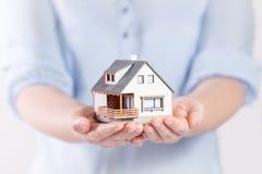 Haus in den Händen der Frau Lizenzfreies Stockfoto