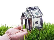 Haus in der Hand gemacht vom Geld lokalisiert Lizenzfreie Stockbilder