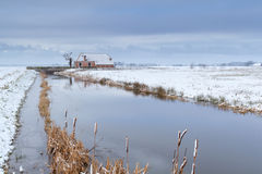 Haus durch Fluss im Schnee auf niederländischem Ackerland Stockfoto