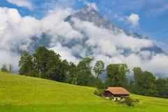 Haus in einer Wiese des Grases nahe hohem Berg Stockfoto