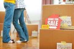 Haus für Verkaufszeichen und Paare im Hintergrund Lizenzfreie Stockfotografie