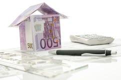 Haus gemacht vom Geld auf einem Arbeitsschreibtisch Stockbilder