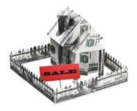 Haus gemacht vom Geld mit einem Zeichen für Verkauf Lizenzfreies Stockbild