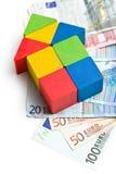 Haus gemacht von den hölzernen Bauklötzen mit Eurogeld Lizenzfreie Stockfotografie