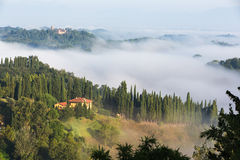 Haus in grünem und nebeligem Toskana-Abhang lizenzfreie stockfotografie