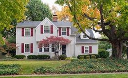 Haus im Fall mit roten Fensterläden Lizenzfreie Stockbilder