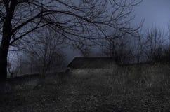 Haus im Nebel nachts im Garten, Landschaft des Geisthauses im dunklen Wald stockfoto