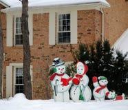 Haus im Winter und in der Schneemann-Familie Lizenzfreie Stockfotografie