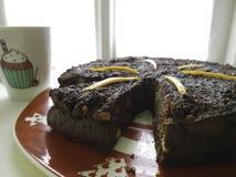 Haus machte den Kuchen, der vom Vorderseite mit einem kleinen Kuchen gesehen wurde zu zeichnen auf einer Schale lizenzfreies stockbild