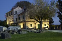 Haus mit alten Ruinen im Vordergrund in Salona, Kroatien Stockbild