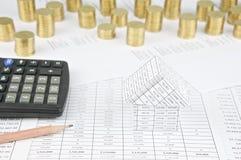 Haus mit Bleistift und Taschenrechner haben Goldmünzen als Hintergrund Stockbild