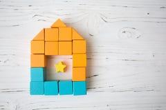 Haus mit der Fenstergestalt von den hölzernen Würfeln des Spielzeugs, liegend auf weißem hölzernem Hintergrund Stockfoto