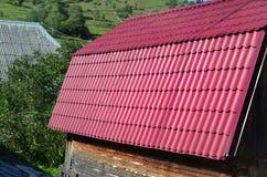 Haus mit einem Dach hergestellt von den festen Blechtafeln, geformt wie ein altes bis Lizenzfreies Stockbild