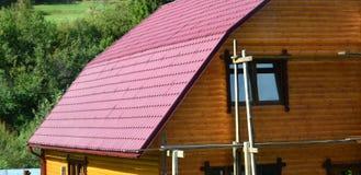 Haus mit einem Dach hergestellt von den festen Blechtafeln, geformt wie ein altes bis Lizenzfreie Stockbilder